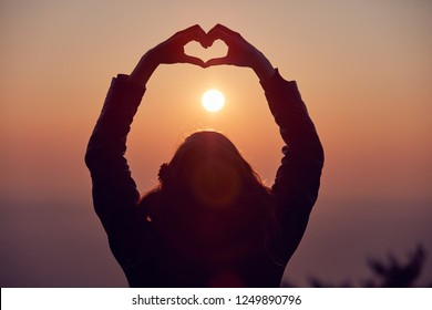 Girl making heart - shape sign with hands at sunset / sunrise time.