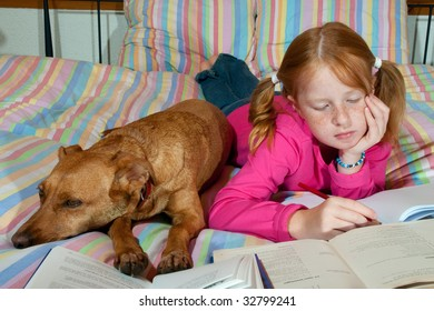 Girl is making homework together with her dog