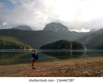 Girl making photo of evening black lake, forest and mountains in Montenegro Durmitor national park