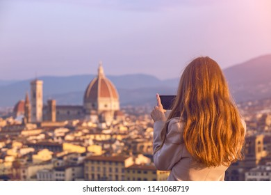 girl making a photo shoot of Florence with the smartphone . Dawn