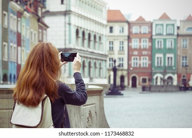 girl making a photo shoot of main square Rynek of polish city Poznan