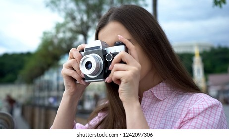 Girl making photo with vintage camera, city tour, vivid impressions, inspiration