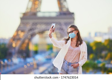 Girl making selfie near the Eiffel tower in Paris and wearing protective face mask during coronavirus outbreak. Pandemic and lockdown in France. Tourist spending vacation in France after quarantine