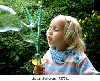 Girl making soap bubbles (image contains some noise)