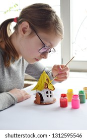 Girl making toys with your own hands, paints a clay house with gouache. Indoors creative leisure for children. Supporting creativity, learning by doing, DIY project, hand craft. Master class of art