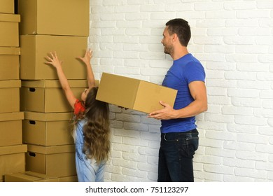 Girl and man with busy faces on white brick wall background. Daughter puts hands up and father puts boxes in pile. Accommodation, moving and family concept. Kid and guy move into new home or move out