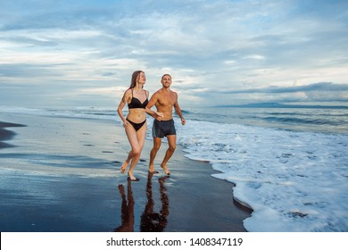 Girl and man on the beach running.
