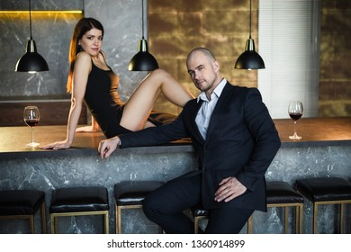 A girl and a man in a restaurant. A girl in a black dress with a slit sitting on the bar in a restaurant looking at the camera, sitting next to a guy in a black suit.