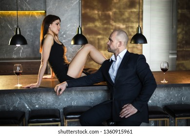 A girl and a man in a restaurant. A girl in a black dress with a slit sitting on the bar in a restaurant looking at a guy in a black suit.