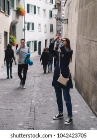 Girl and man shooting by mobile phone in the street.