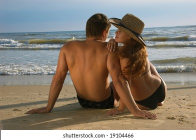 The girl and man sit on a coast of the sea