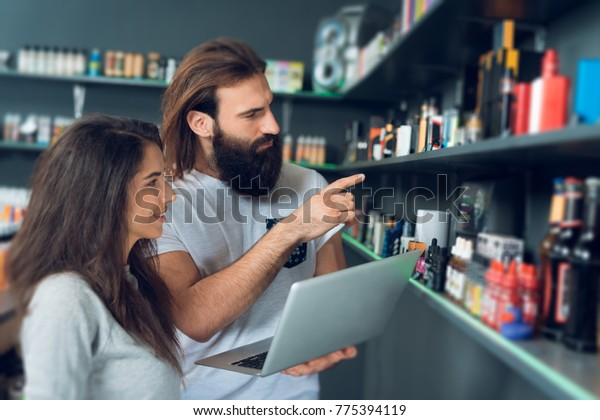 A girl and a man are standing with a laptop in an electronic cigarette store. They choose smoking devices and liquids.