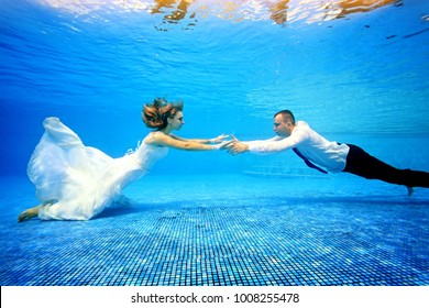 Girl and man in wedding dresses swim underwater in the pool to meet each other. Horizontal orientation. A view from under the water