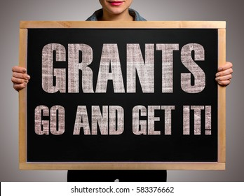 Girl (manager, student, businesswoman) in casual clothes holding a black chalk board with the text Grants go and get it