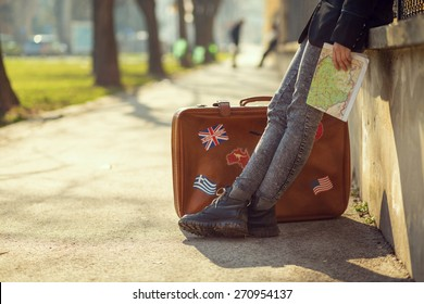 A girl with a map and suitcase. Focus on the boots.