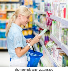 Girl at the market choosing cosmetics among the great variety of products. Concept of consumerism, retail and purchase