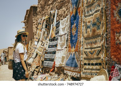 Girl at marketplace staring arabic carpets in Marrakesh