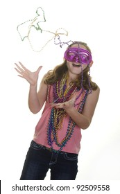 Girl in mask catching mardi gras beads