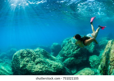 A  girl with mask exploring underwater in the Mediterranean Sea