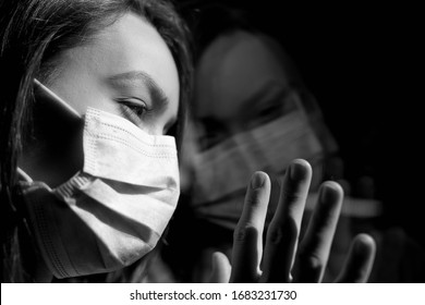 Girl in a mask looks out the window, in quarantine with reflection. Gloomy frame, quarantine. Powerful outbreak of coronavirus.