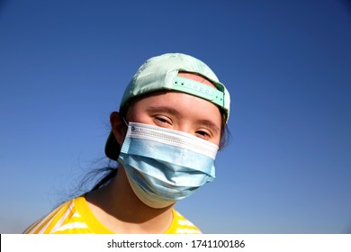 Girl in a mask on her face on background on a blue sky
