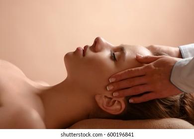 Girl massage therapist doing head massage beautiful brunette girl