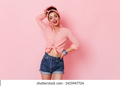Girl in massive earrings, pink shirt and denim shorts posing on pink background with arm raised