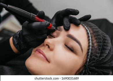 Girl master beautician makes eyebrow tattoo
