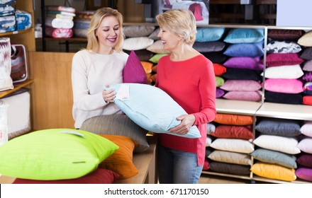 Girl and mature woman customers looking for pillow in home textile shop