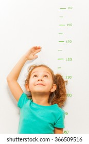Girl measure height with hand looking up