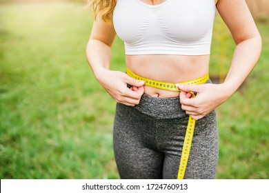 a girl measures her waist after a workout