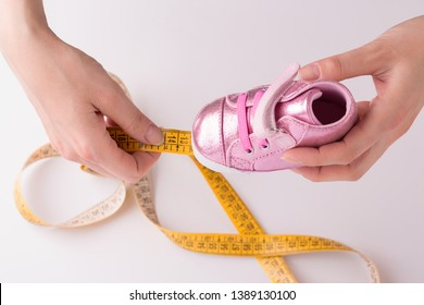 The girl measures the size of children's shoes yellow tape size. Measurement of children's shoes. Children's shoes. Growth foot baby.