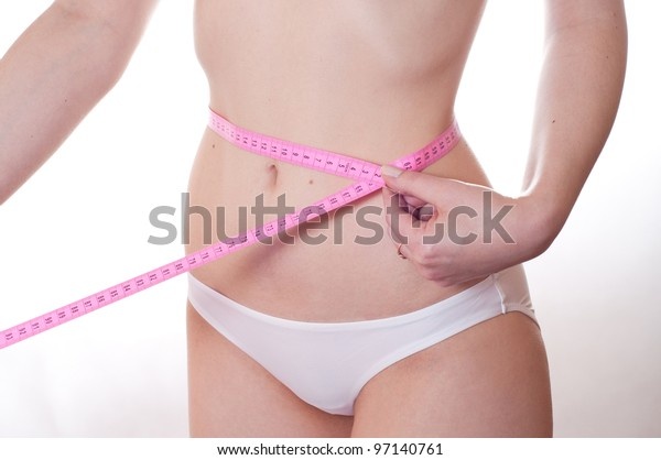The girl measures waist volume on a white background