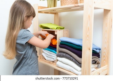 The girl is measuring her mother's clothes and shoes. Order in the closet. Smart storage system. Capsule wardrobe. The girl plays and puts mother's clothes in order or chaos. Wardrobe order.
