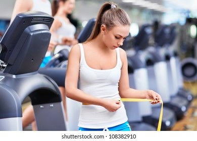 Girl with a measuring tape in fitness club