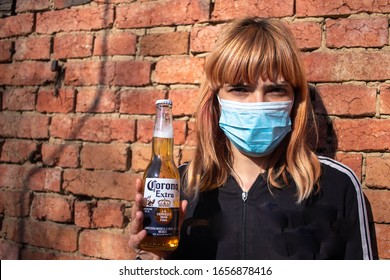 Girl with medical mask holding Corona Beer. In the middle of cornavirus (covid-19) pandemic and global health crisis. Mexican brewery brand Corona shares the same name with this vicious virus.