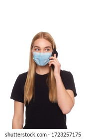 The girl in the medical mask is in home isolation and is talking on the phone with relatives. Studio photography on a white background