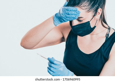 The girl in the medical mask looks at the thermometer and frowns. High temperature in a sick person. Virus epidemic concept. Close Up