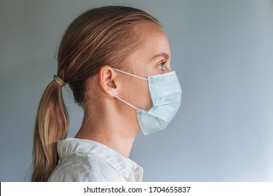 A girl in a medical mask on a gray background. copy space