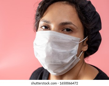 Girl in a medical mask on a pink background. Doctor