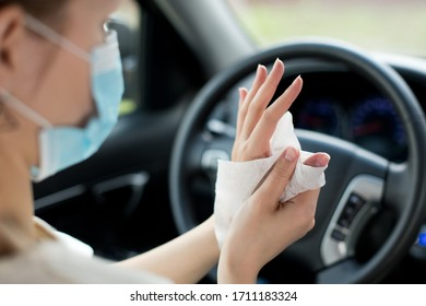girl in a medical mask rubs her hands with an antiseptic napkin against the background of a steering wheel in a car