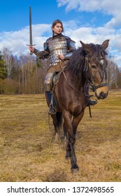 Girl in medieval knight's armor 15 century on a horse against the background of the forest
