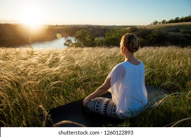 Girl meditates sitting on a beautiful meadow at sunset