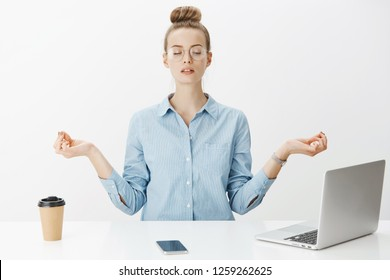 Girl meditating at work sitting in lotus pose with nirvana orbs near laptop and smartphone trying relax and get rid of pressure and stress posing calm and peaceful against gray background in glasses