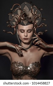 girl Medusa headdress of gold color on a black background.