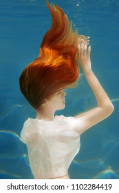 Girl mermaid with healthy shiny beautiful long hair. Underwater scene. A woman, a fashion model in the water in a beautiful dress swims like a fish.