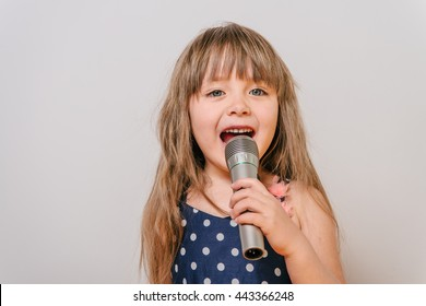 Girl with a microphone. little girl with a microphone. cute little girl singing with a microphone. karaoke. girl sings joyfully. girl singer. the little singer.