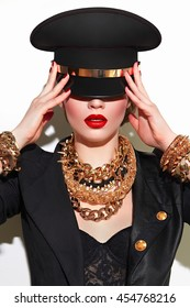 Girl in military cap with red lips gold ornaments in the style of steam-punk. Military fashion.
