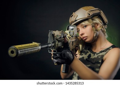 the girl in military overalls airsoft posing with a gun in his hands on a dark background in the haze