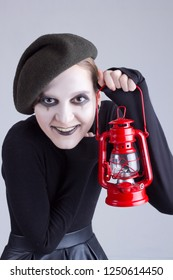 Girl mime with red gas lamp on a gray background